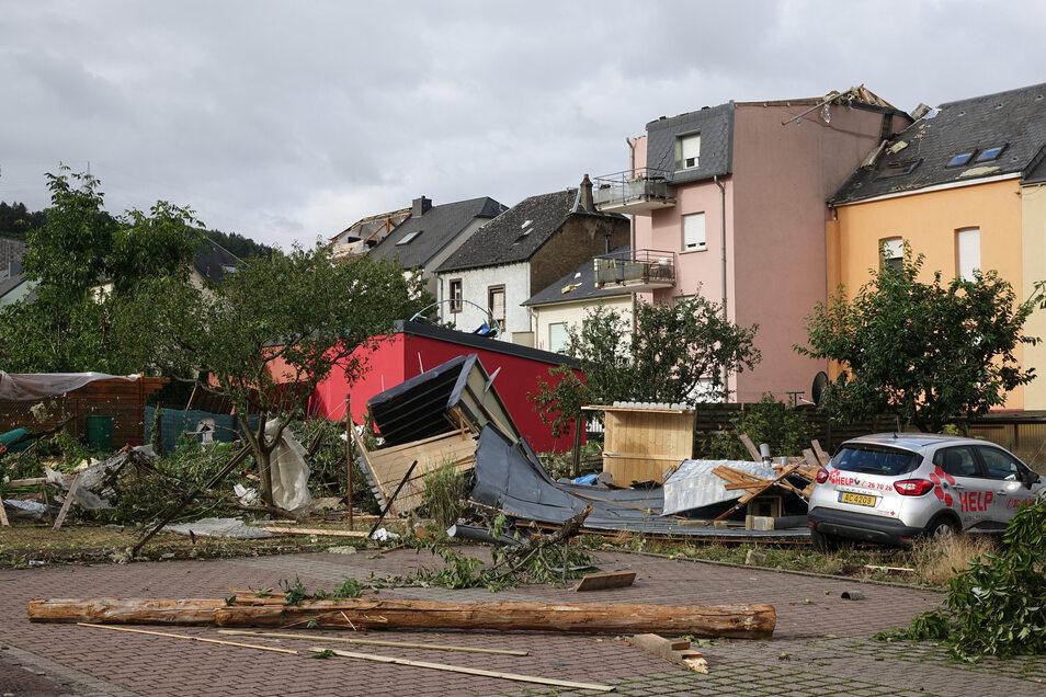 Luxemburg, Petingen: Nach einem schweren Unwetter mit einem Tornado liegen Trümmer auf einem Platz.