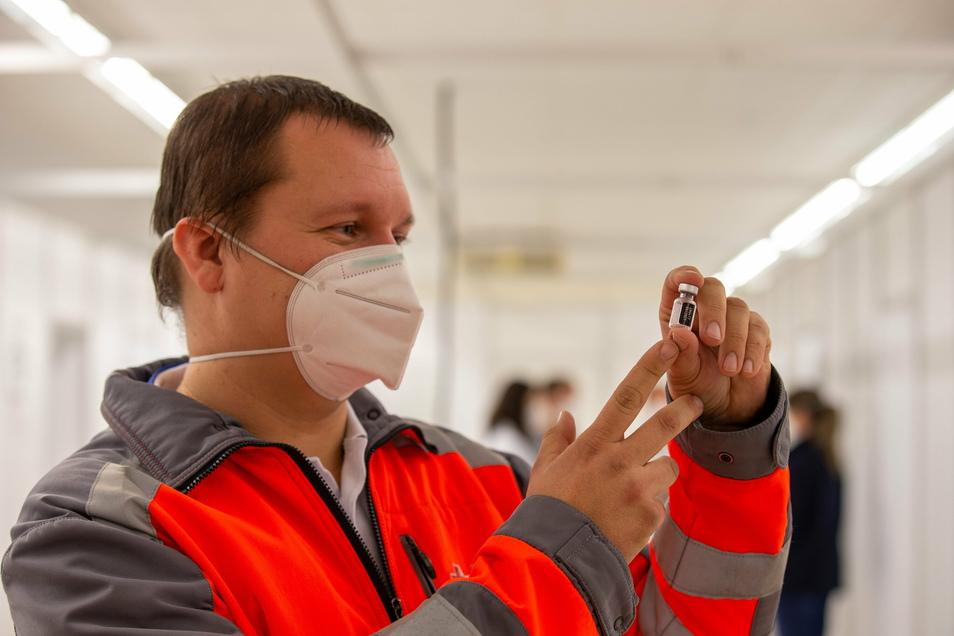 Christian Thie, Leiter des Impfzentrums in Pirna-Jessen, hält ein leeres Fläschchen des Corona-Impfstoffs in der Hand.
