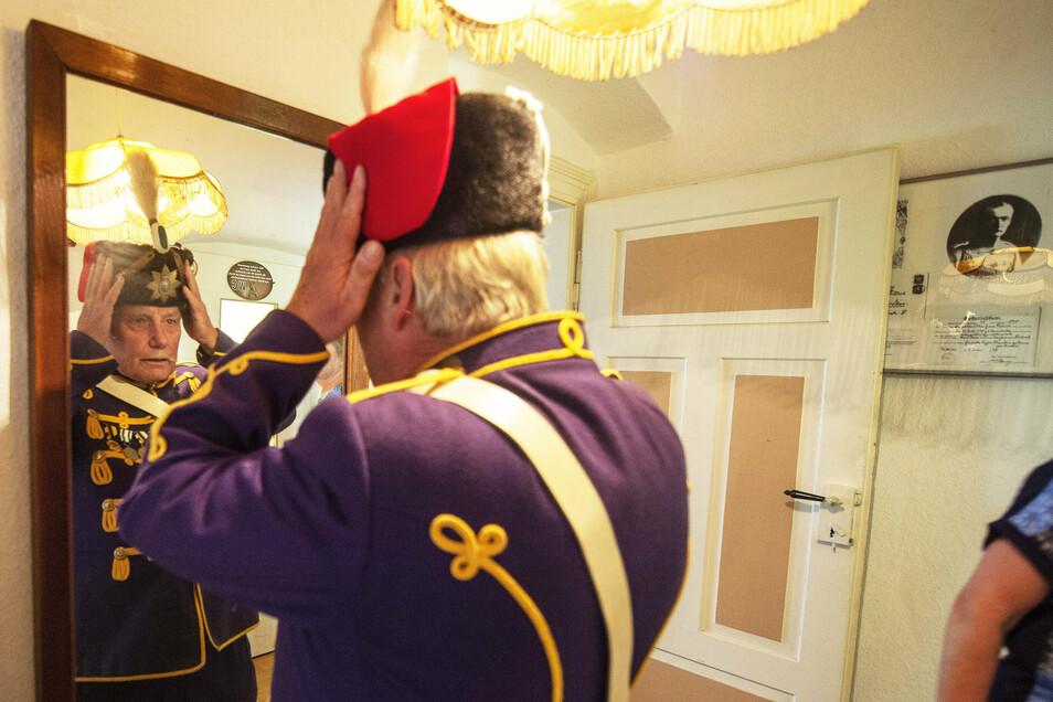 Lothar Fiebig steht sich vor dem Spiegel die Husarenmütze auf.