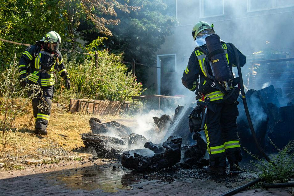 Brennende Holzstämme mussten Feuerwehrleute am Freitagmittag in Bischofswerda-Geißmannsdorf löschen.