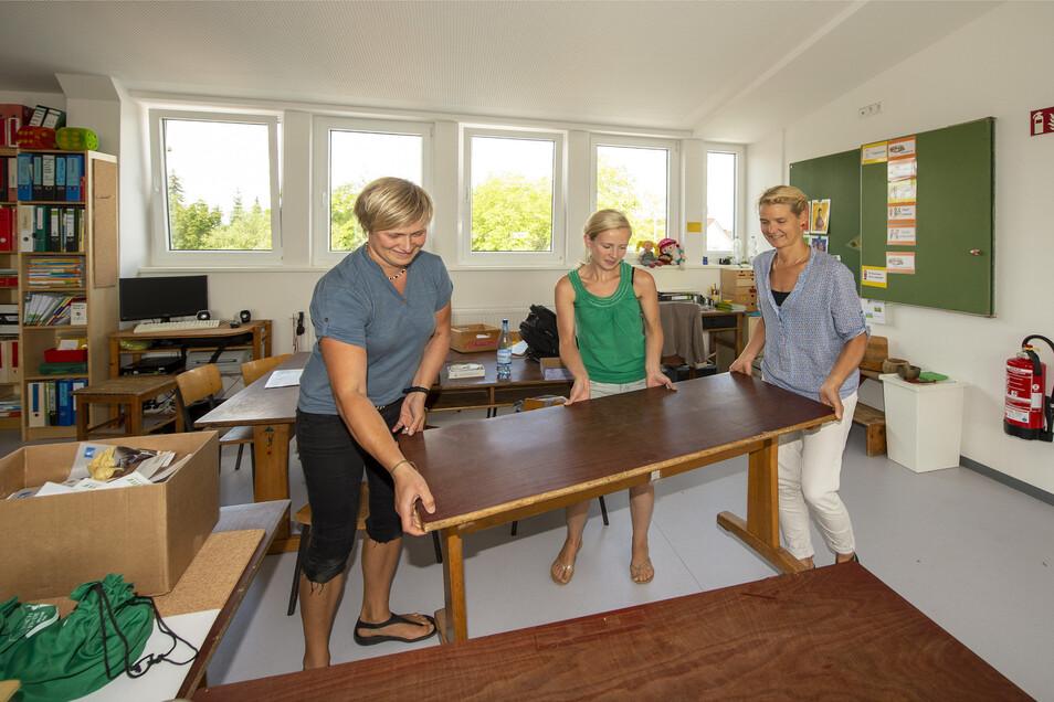 Die Klassenleiterinnen Jule (l.) und Simone (r.) räumen mit Referendarin Laureen eines der neuen Klassenzimmer im Dachgeschoss ein.