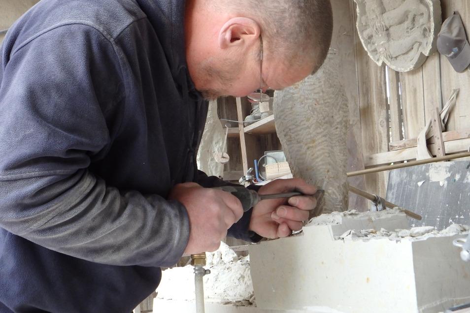 Bildhauer Dirk Bretschneider schlägt den fehlenden Fuß aus dem Sandstein.