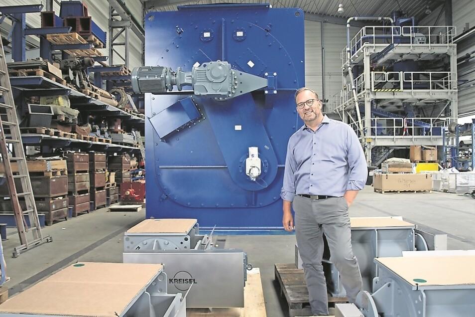 Geschäftsführer Wolfram Kreisel vor der größten im Unternehmen gebauten Zellenradschleuse. Die 3,50 hohe Anlage ist für eine Zementfabrik in den USA, steht kurz vor ihrer Verschiffung nach Übersee und ist somit auch Bildnis für den Neustart der Krauschwit