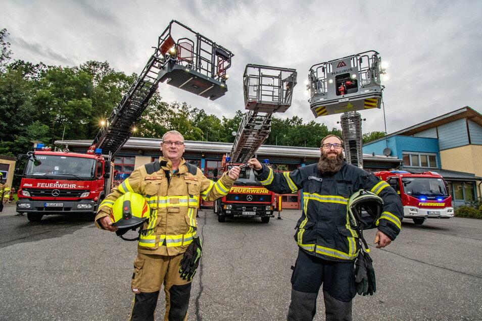 Uwe Beck (l.) von der Feuerwehr Roßwein gibt den Schlüssel des Döbelner Drehleiterfahrzeuges an René Weißbach zurück.