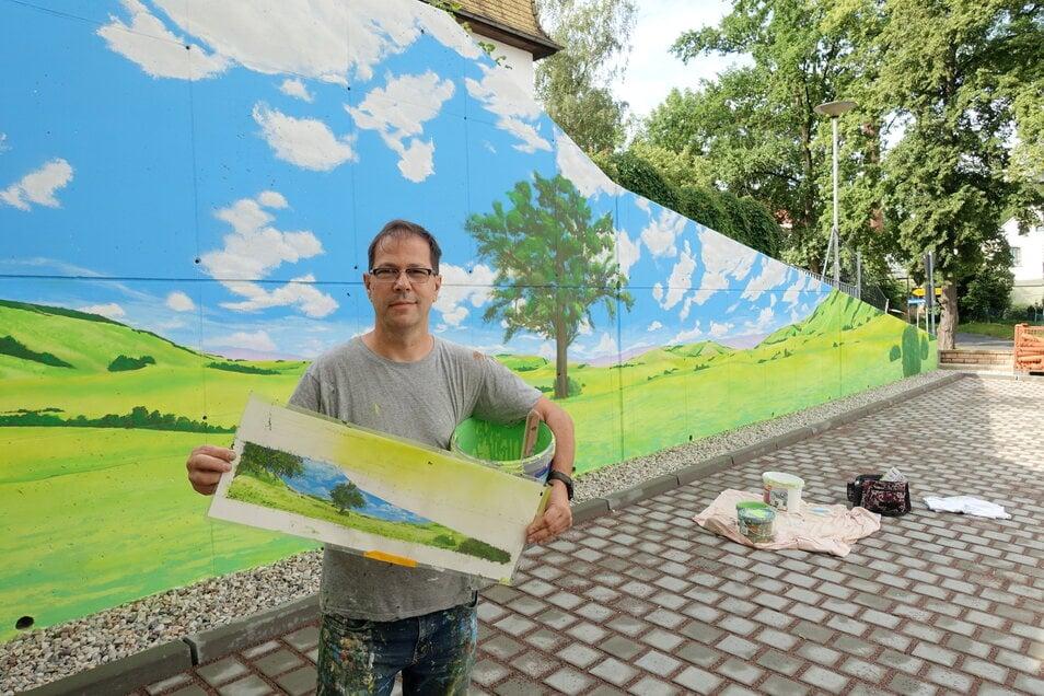 Der Graffiti-Künstler Frank Schäfer kann auch mit dem Pinsel. An der Stützmauer neben dem Neubau der GWG hat er eine Hügellandschaft entstehen lassen.