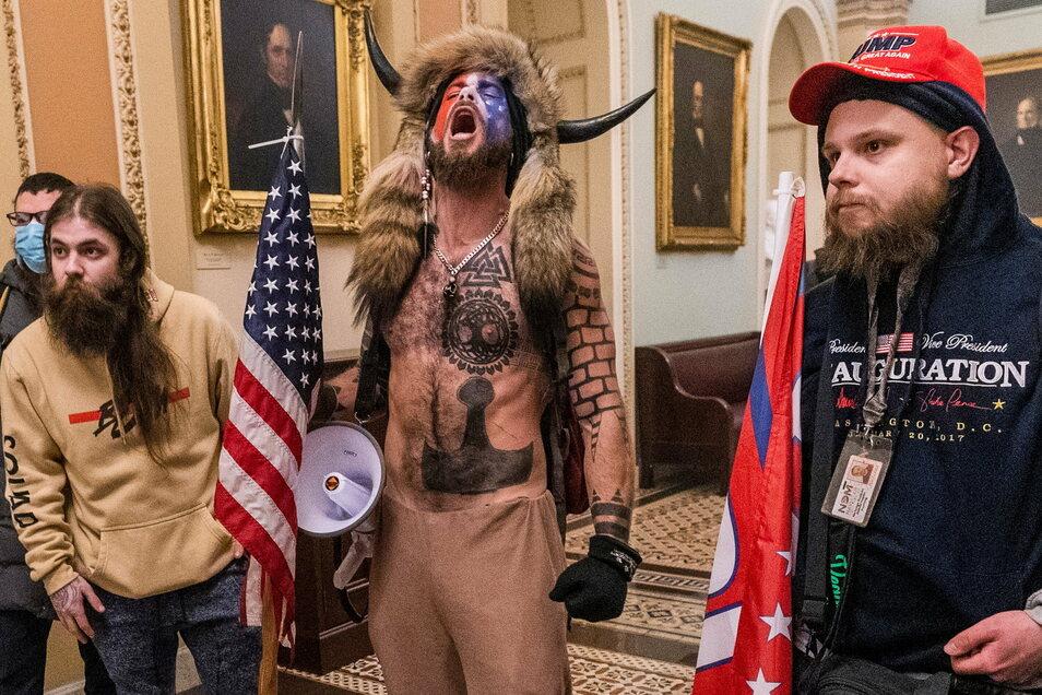 Unter den Eindringlingen in das US-Kapitol am Mittwoch in Washington ist auch Jake Angeli (M), selbst ernannter Schamane und Anhänger des Verschwörungskults QAnon.