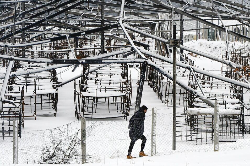 Ein Mann geht durch den Schnee im abgebrannten Lager Lipa.
