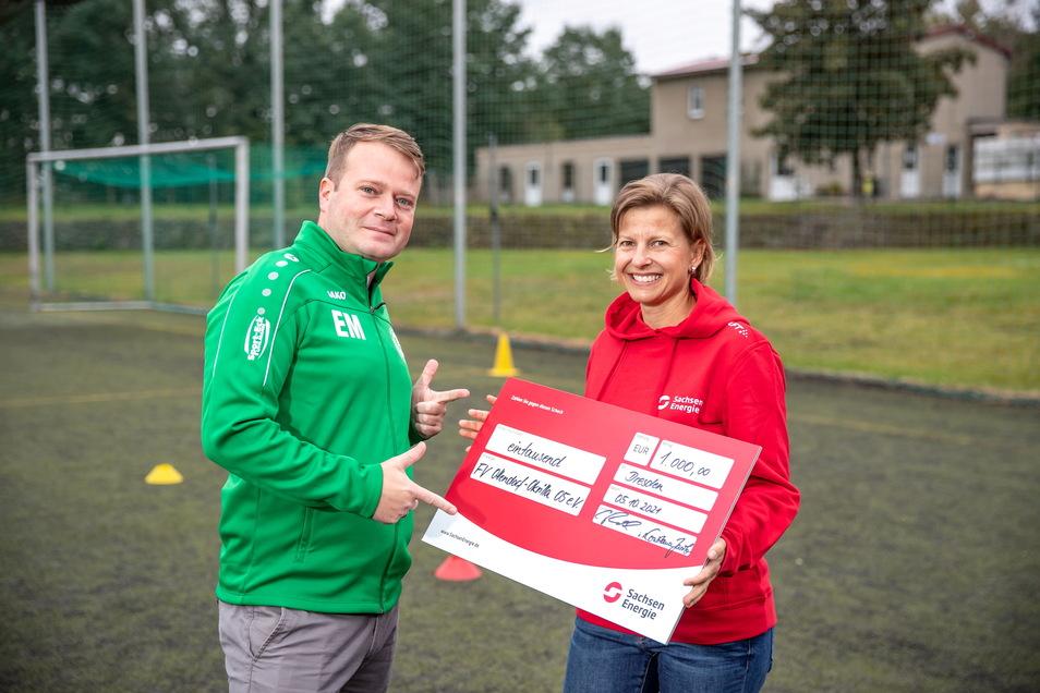 Constance Jacob von Sachsen-Energie überreicht einen 1.000 Euro-Scheck an Eric Mantke vom Fußballverein Ottendorf-Okrilla 05.