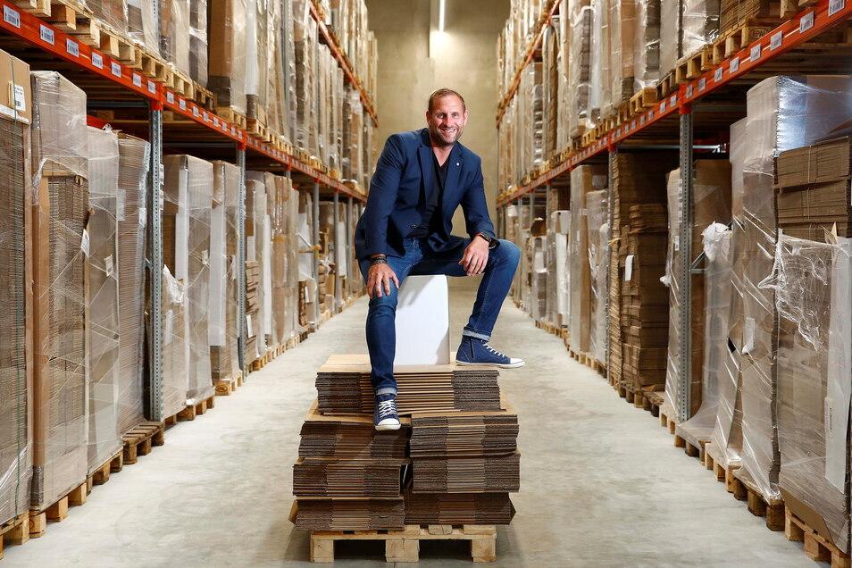 Boxxco-Geschäftsführer Michael Arndt kann sich freuen. Zu seiner Firma gehört jetzt auch eine große Lagerhalle. Hier sitzt der Chef auf einem Papphocker, der vom Unternehmen selbst entwickelt wurde.