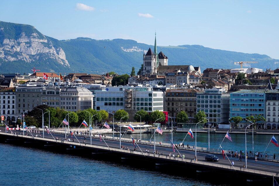 Schweiz, Genf: Menschen überqueren eine mit US-amerikanischen und russischen Nationalflaggen geschmückte Brücke.