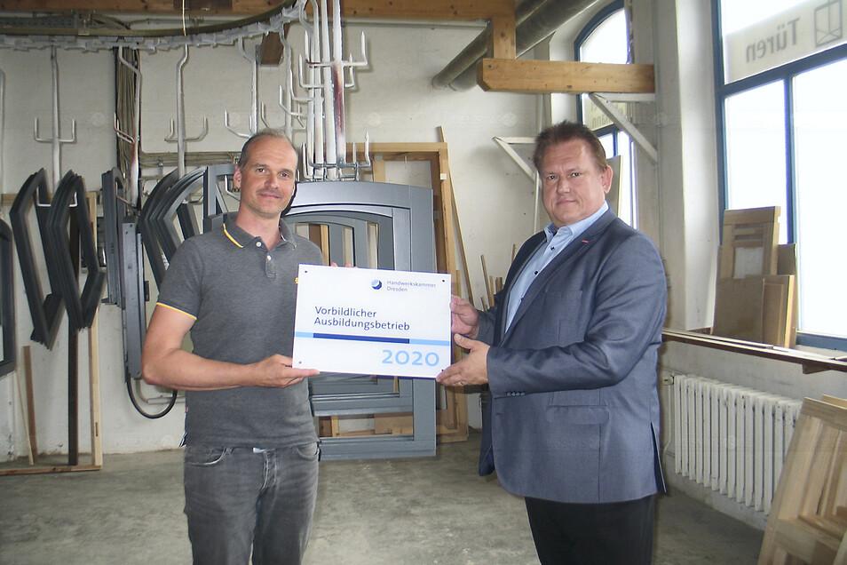 """Alexander Hanisch (li.) ist seit einem Jahr Chef der Tischlerei Lehmann GmbH in Weißwasser. Jetzt würdigte Dr. Andreas Brzezinski, Hauptgeschäftsführer der Handwerkskammer Dresden, die Firma als """"Vorbildlichen Ausbildungsbetrieb 2020""""."""