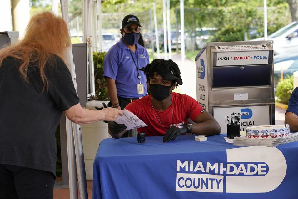 Wahlhelfer Najeh Fisher (M) nimmt für Wahlen im Bezirk Miami-Dade den Stimmzettel einer Wählerin entgegen.