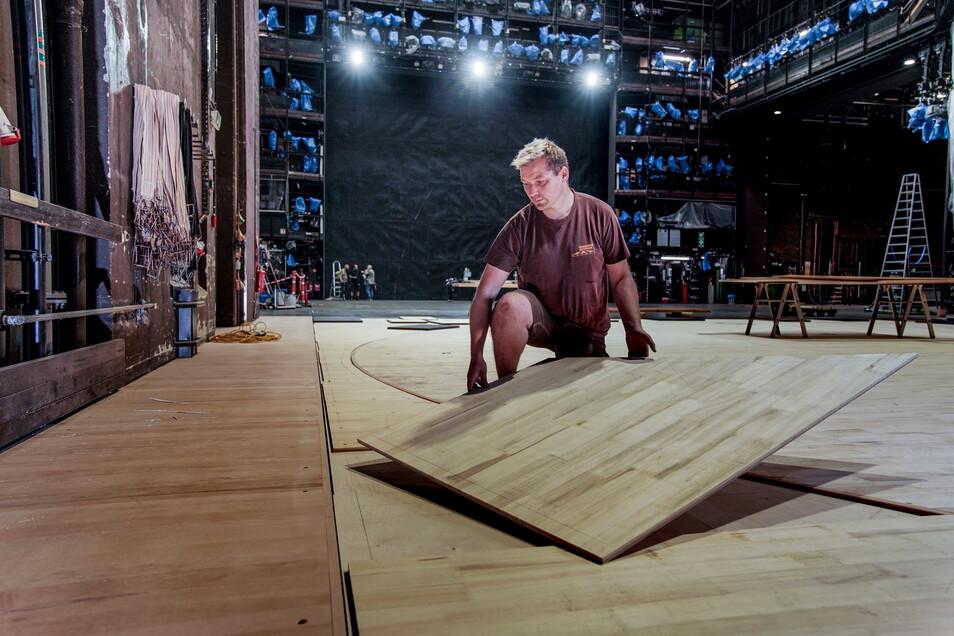 Dirk Lattermann verlegt die letzten Teile an der Drehbühne. Diese Woche führen die Bühnenbauer noch die abschließenden Arbeiten an der Oberfläche aus, so das Verschleifen.
