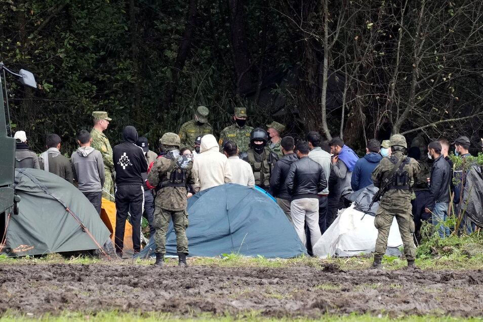 Migranten, die an der Grenze zu Belarus festsitzen, werden von polnischen Beamten umstellt. Polens Grenzschützer haben im August an der Grenze zu Belarus rund 3.500 Versuche einer illegalen Einreise registriert.