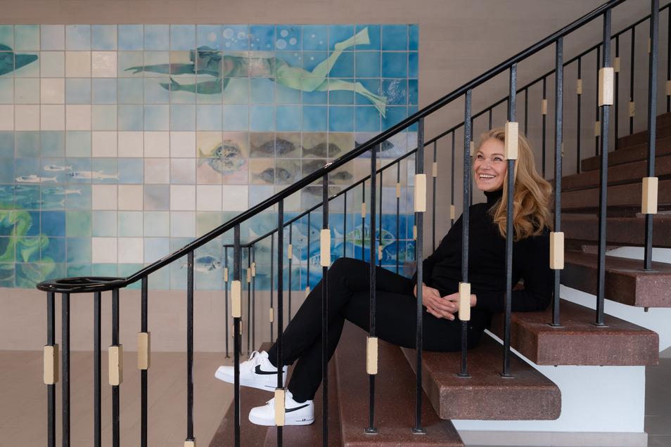 Rica Reinisch sitzt in der neuen Schwimmhalle Freiberger Straße auf einer Treppe, die von früher erhalten geblieben ist. Als 15-Jährige gewann sie 1980 bei Olympia dreimal Gold.