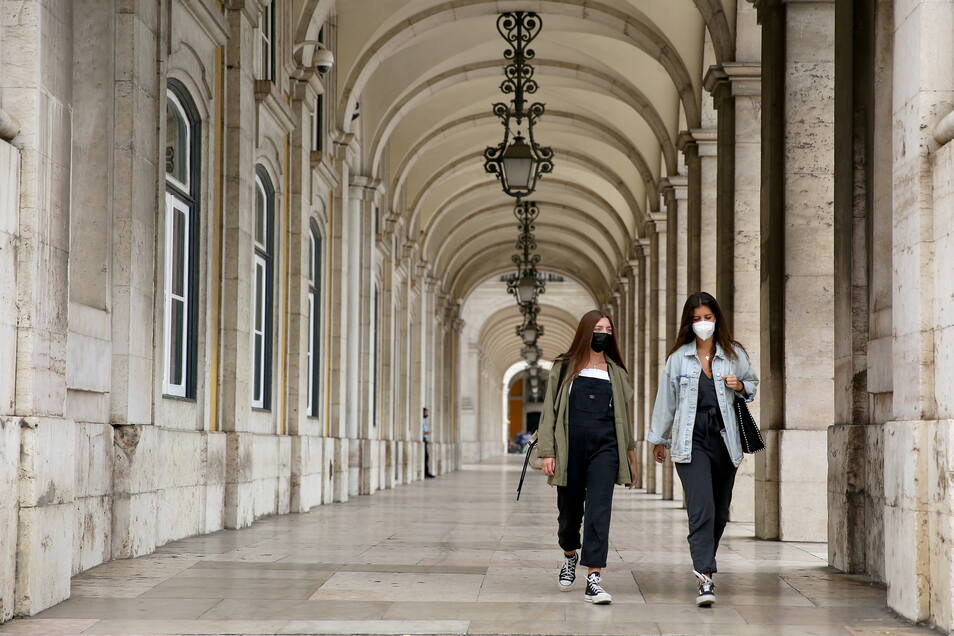 Zwei Frauen mit Mund-Nasen-Schutz spazieren in der Innenstadt von Lissabon.