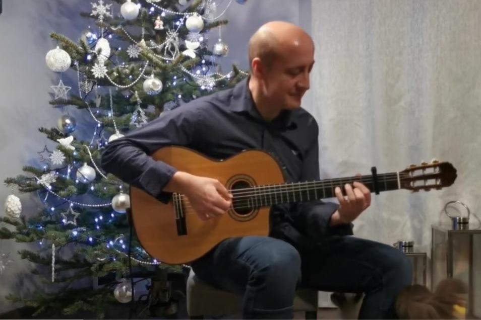 Weihnachtsbaum, Gitarre, Katze und Musiker Bartłomiej Filipowicz.