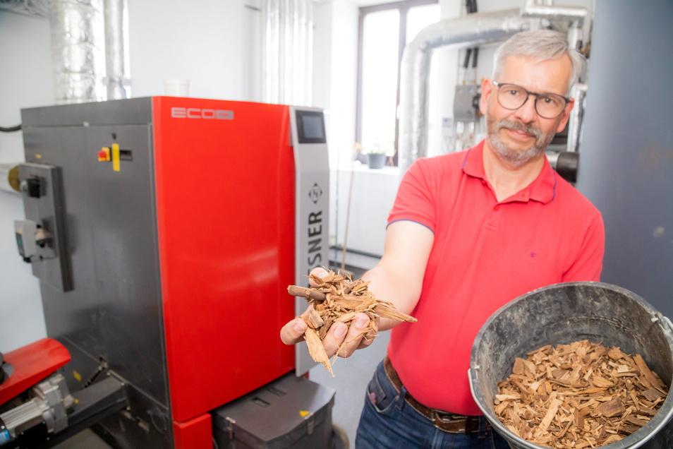 Kois-Geschäftsführer Andreas Schneider zeigt einen Eimer voll mit Holzhackschnitzeln. Der Kodersdorfer Bauhof wurde damit ausgerüstet und ist jetzt klimafreundlich aufgestellt.