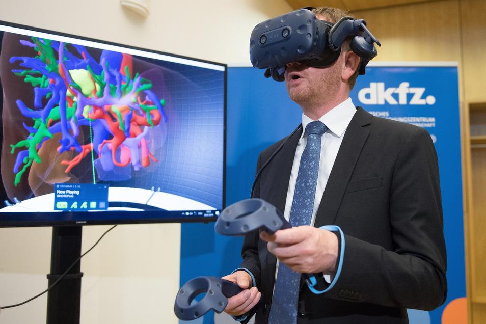 Ministerpräsident Michael Kretschmer vor einem Jahr im Nationalen Zentrum für Strahlenforschung in der Onkologie: Mithilfe einer VR-Brille betrachtet er eine vom Krebs befallene Leber. Kretschmer sieht Krebsforschung künftig auch in der Lausitz. Das vorge