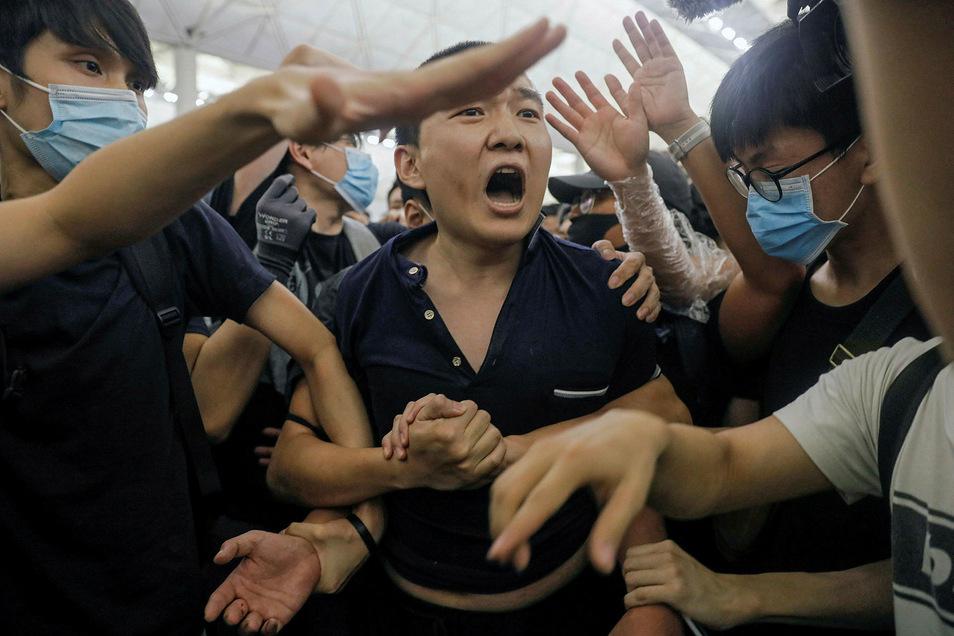 Demonstranten am Flughafen umringen einen Mann, dem sie vorwerfen ein chinesischer verdeckter Ermittler zu sein.