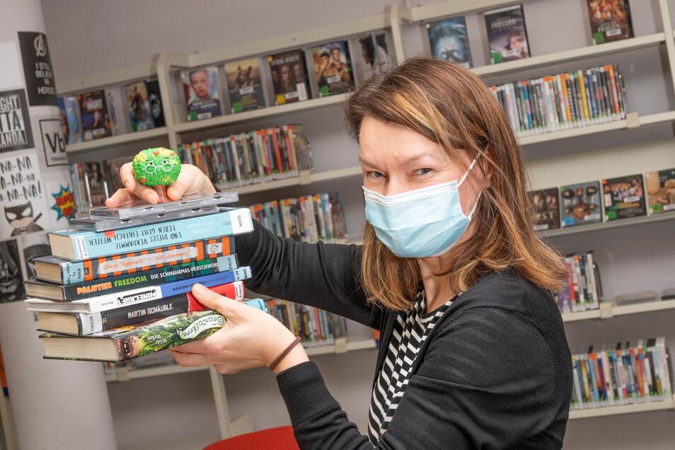 """Birgit Herold zeigt eine Auswahl der Bücher, die zuletzt in der Kinder- und Jugendbibliothek besonders gern gelesen wurden. Die Figur oben ist ein """"Tonie"""" - über den sich Hörspiele abspielen lassen."""