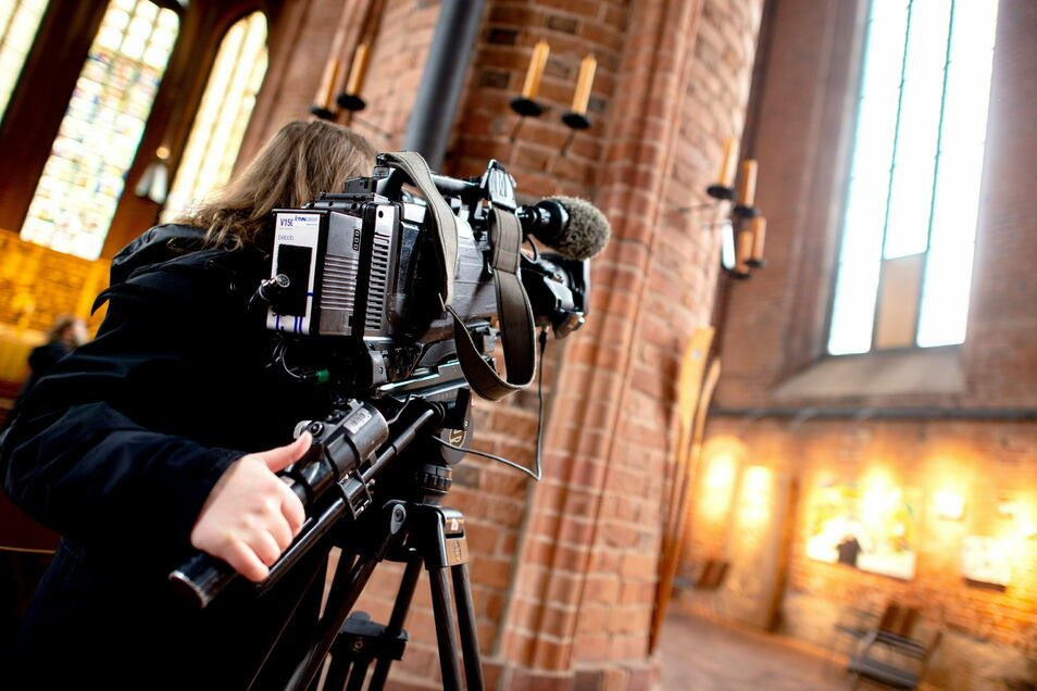 Eine TV-Journalistin filmt während eines Ortstermins im Zivilprozess um das Reformationsfenster in der Marktkirche die bisherigen Fenster der Kirche.