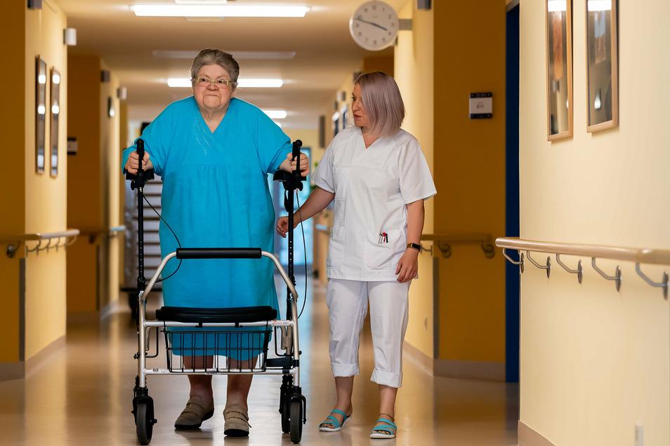 Trotz Rollator fällt Brigitte Weigelt das Laufen noch schwer. Schwester Lysann Dökert unterstützt sie auf dem Gang der Chirurgischen Klinik im Krankenhaus Bischofswerda.