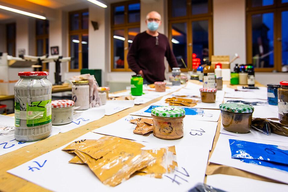Jens-Uwe Röhl am Tisch, auf dem die benötigten Farben für die Leinwände vorsortiert und beschriftet sind. In der Kreativwerkstatt ist alles deponiert, was der Kartoffeldrucker so braucht. Hier ist die Ausgabe der nötigen Materialien – nur die Karto