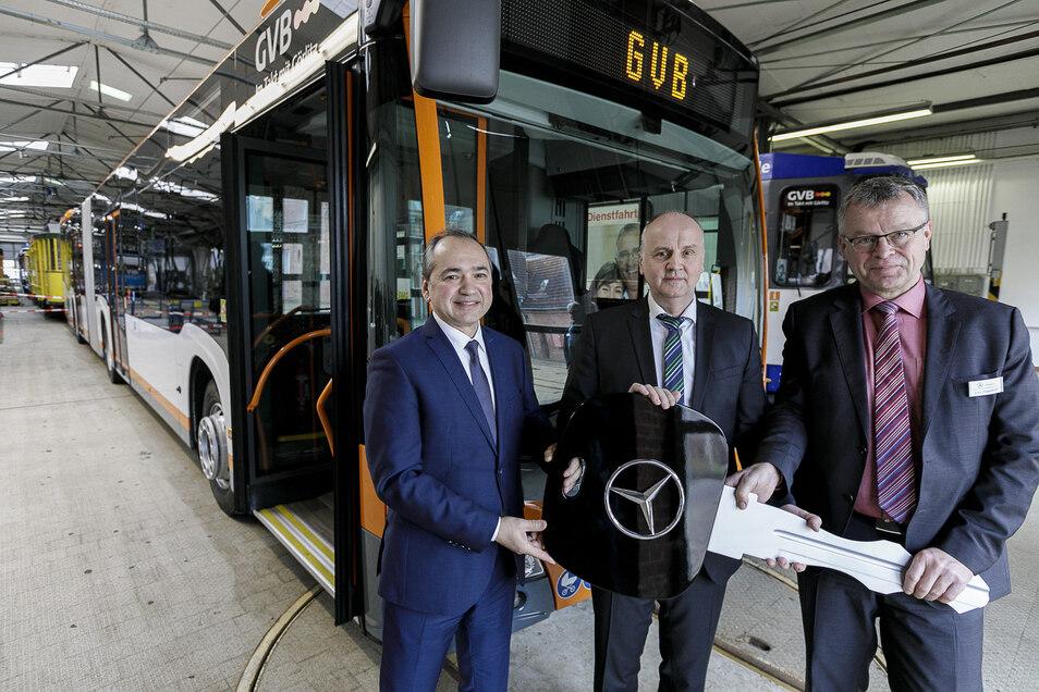 Uwe Mauerhoff (r.), Vertriebsbeauftragter bei Mercedes-Benz Omnibusse, übergibt einen symbolischen Schlüssel für den neuen Hybridbus (im Hintergrund) an  Oberbürgermeister Octavian Ursu (l.) und GVB-Geschäftsführer Andreas Trillmich.