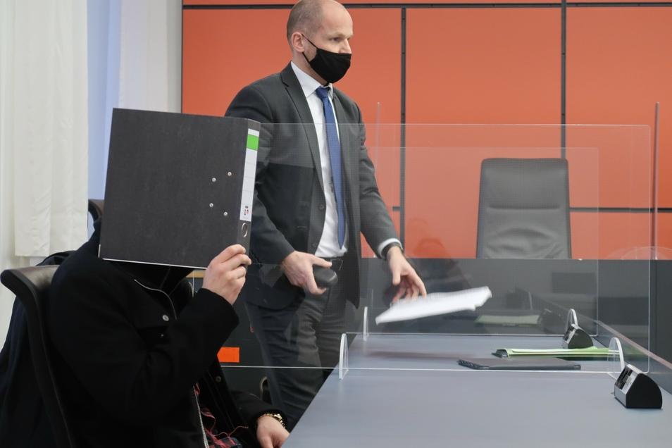Der Angeklagte David P. versteckt zum Auftakt des Berufungsprozesses am Landgericht Dresden sein Gesicht hinter einem Aktenordner. Dahinter Carsten Brunzel, der Verteidiger des Dresdner Youtubers.