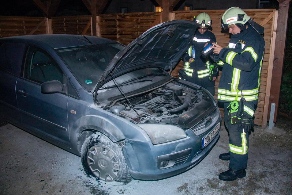 Feuerwehrleute begutachten das Brandfahrzeug im Bischofswerdaer Ortsteil Weickersdorf.