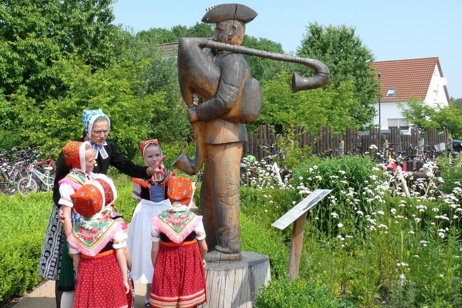 Sorbische Kulturpflege: Angelika Balzke erklärt hier den Kindern aus dem Dorf, welche Rolle einst der letzte Dudelsackspieler Hans Schuster im sorbischen Leben von Trebendorf spielte.
