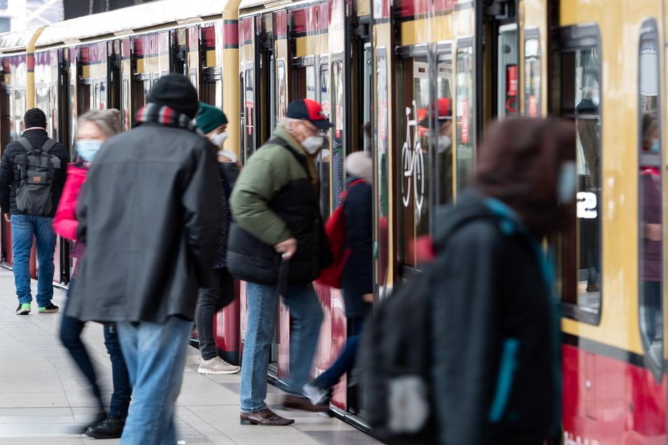 Fahrgäste mit Mund-Nasen-Bedeckungen steigen am Bahnhof Friedrichstraße in Mitte in eine S-Bahn.