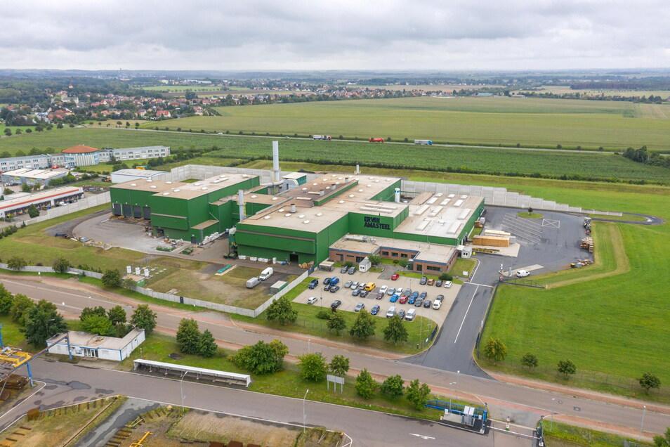 Die große Produktionshalle in der Mitte des Stahlwerks soll künftig bis an die Industriestraße (vorn) reichen. Auf dem Dach sind noch deutlich die Spuren des Brandes vom Juni 2019 zu sehen.