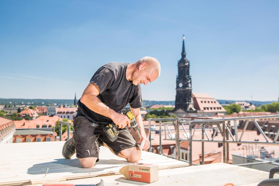 Hoch über der Neustadt arbeitet Zimmermann Andreas Kappel an der Schalung des neuen Dachstuhls für das Palatium am Palaisplatz.