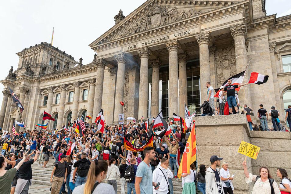 Teilnehmer einer Kundgebung gegen die Corona-Maßnahmen stehen Ende August 2020 auf den Stufen zum Reichstagsgebäude, zahlreiche Reichsflaggen sind zu sehen.