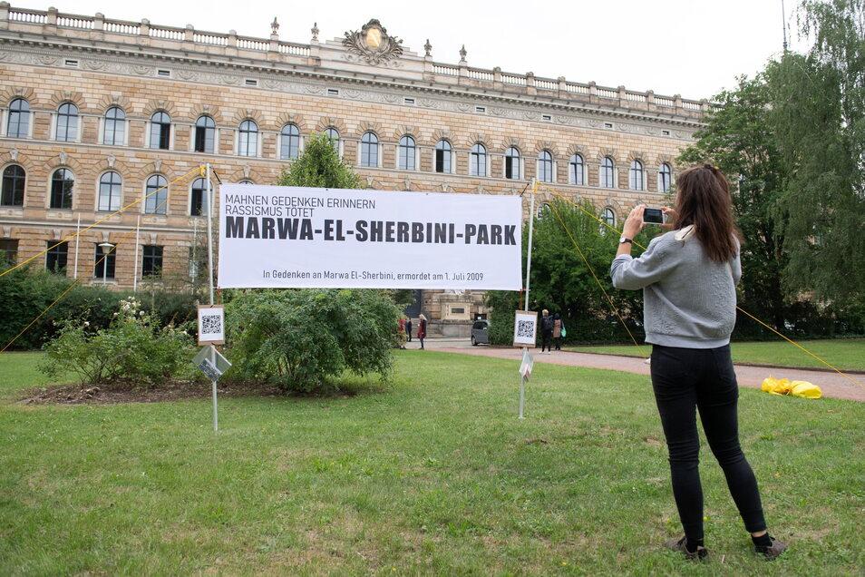 """Ein Banner mit der Aufschrift """"Marwa-El-Sherbini-Park"""" steht vor dem Landgericht."""
