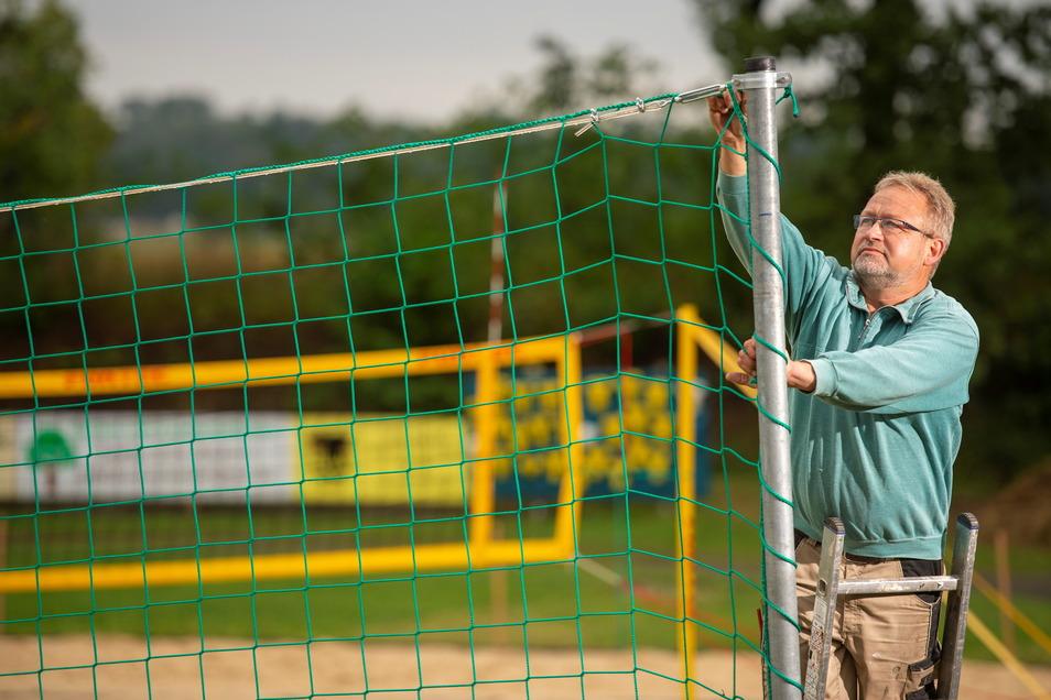 Roland Mehnert, der Platzwart der TSV 1862 Radeburg, baut das Trennnetzes zwischen den beiden neuen Beachvolleyball-Feldern auf.