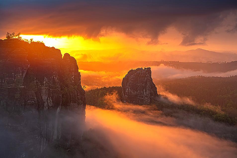 Dramatischer Sonnenuntergang in den Schrammsteinen. Nach einem heftigen Platzregen öffnete sich für einen kurzen Moment noch einmal der Himmel und ließ die letzte Abendsonne in den Nebel scheinen. Ein Farbspektakel Ende Mai, wie ich es so dort oben so noc