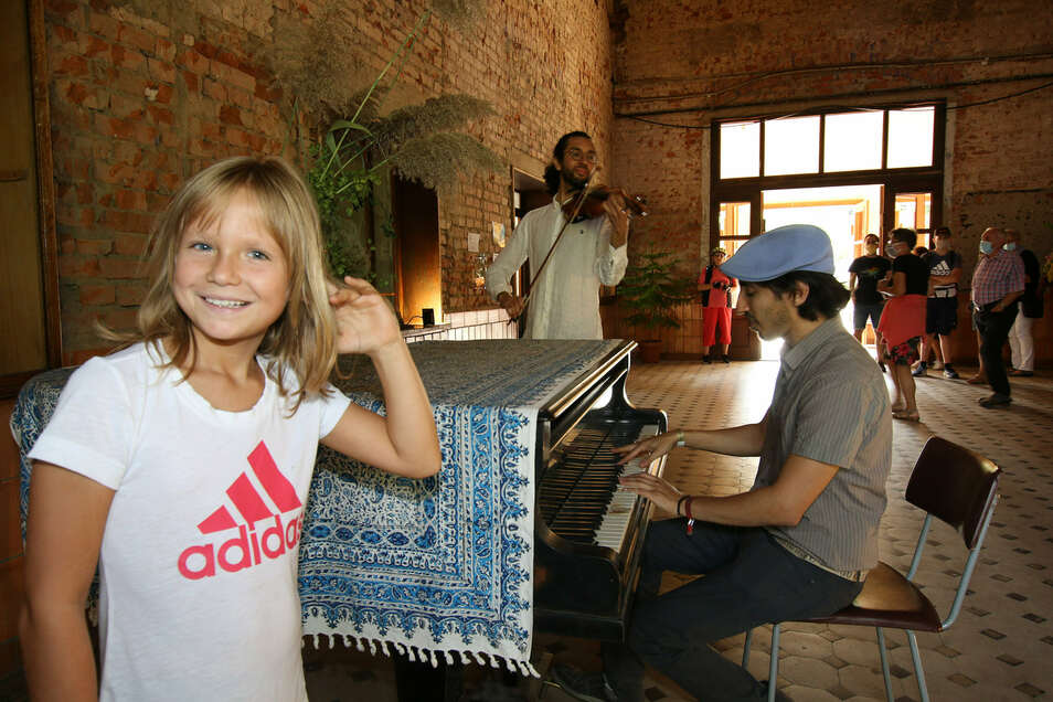 Sina lauscht im Leisniger Kulturbahnhof der Musik, die Ofer aus Israel am frisch restaurierten Flügel und Alireza auf der Violine spielen. Eine Menge Leute nutzten am Sonnabend die Gelegenheit, sich im Bahnhof umzusehen.