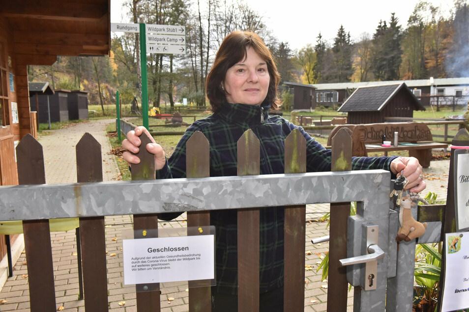 Kassiererin Sylvia Meißner schließt wegen der Corona-Schutzmaßnahmen das Tor zum Wildpark Geising.