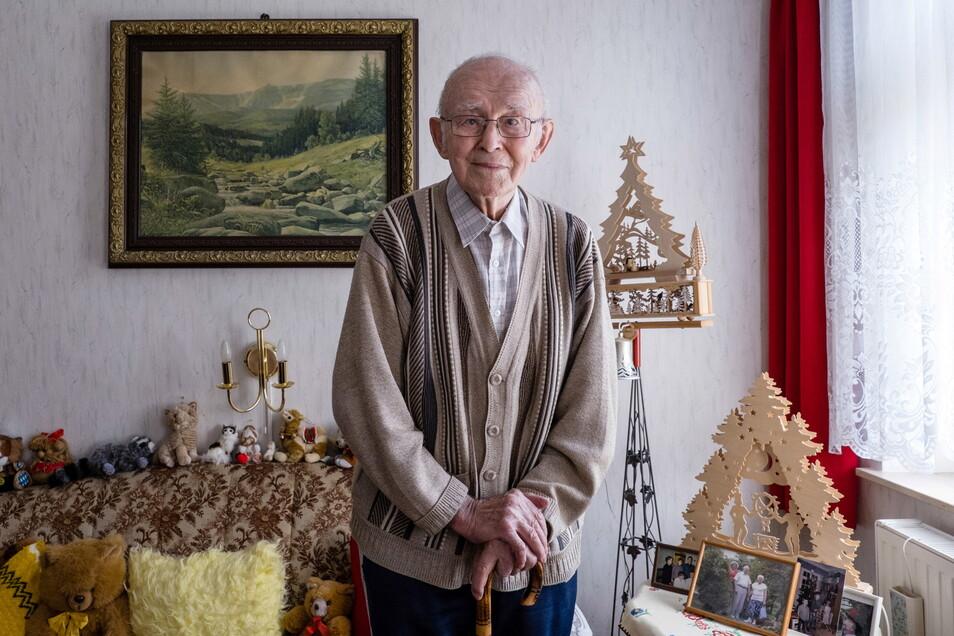 Helmut Friebel steht in seinem Wohnzimmer, das er üppig dekoriert hat – auch mit Bildern von seinem geliebten Riesengebirge.