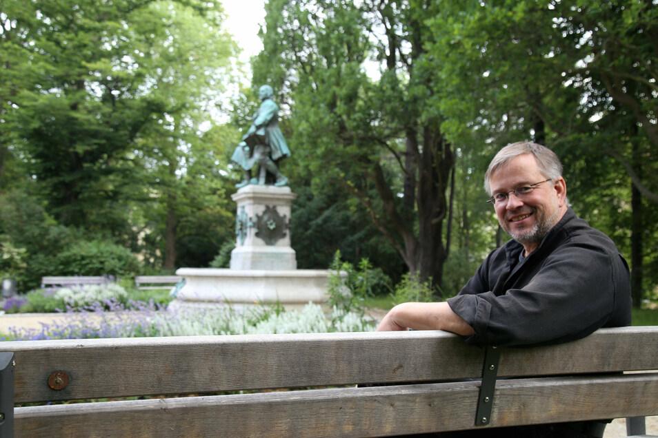 Bürgermeister Michael Wieler sitzt vor dem Jakob-Böhme-Denkmal im Park des Friedens.