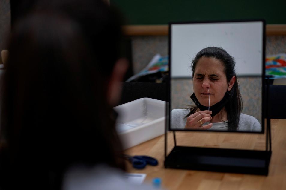 Die Mitarbeiterin einer öffentlichen Schule in Barcelona führt das Stäbchen für einen Selbsttest in ihre Nase ein.