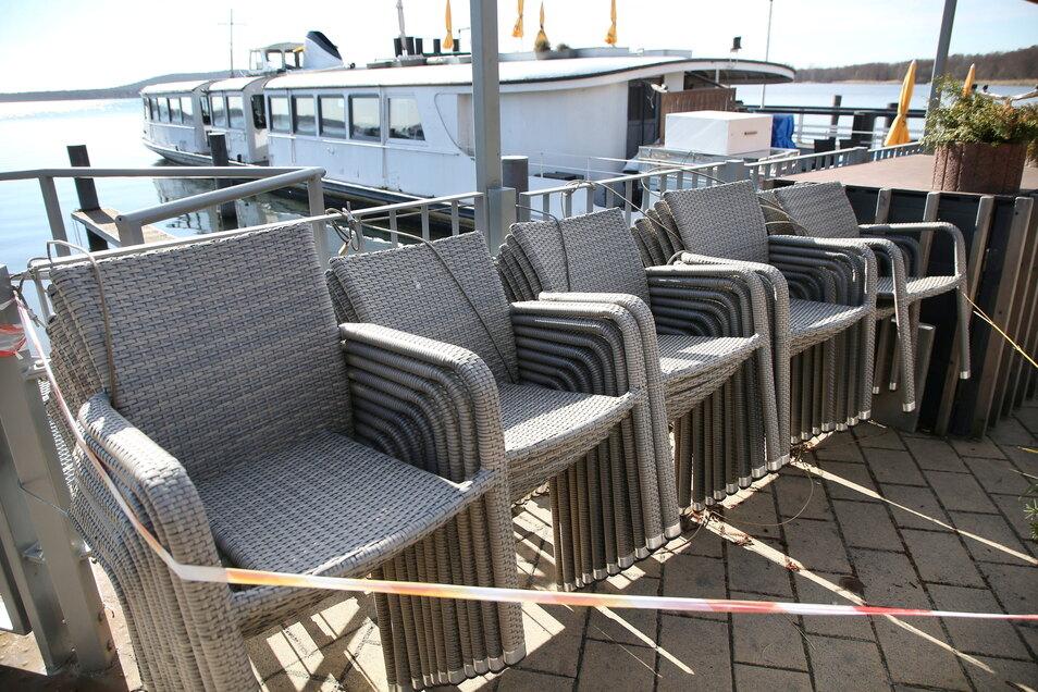 Zusammengestellte Stühle eines geschlossenen Restaurants am Berliner Müggelsee. Über Ostern soll deutschlandweit das öffentliche, private und wirtschaftliche Leben weitgehend heruntergefahren werden.