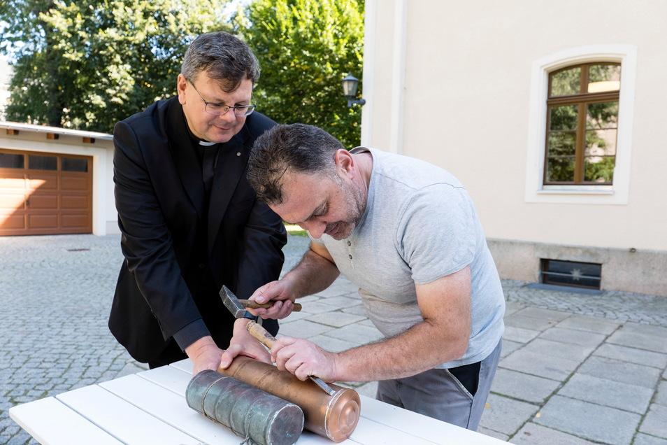 Pfarrer Roland Elsner (links) hilft Hausmeister Jack Murad beim Öffnen der Kartuschen aus der Jauernicker Turmkugel.