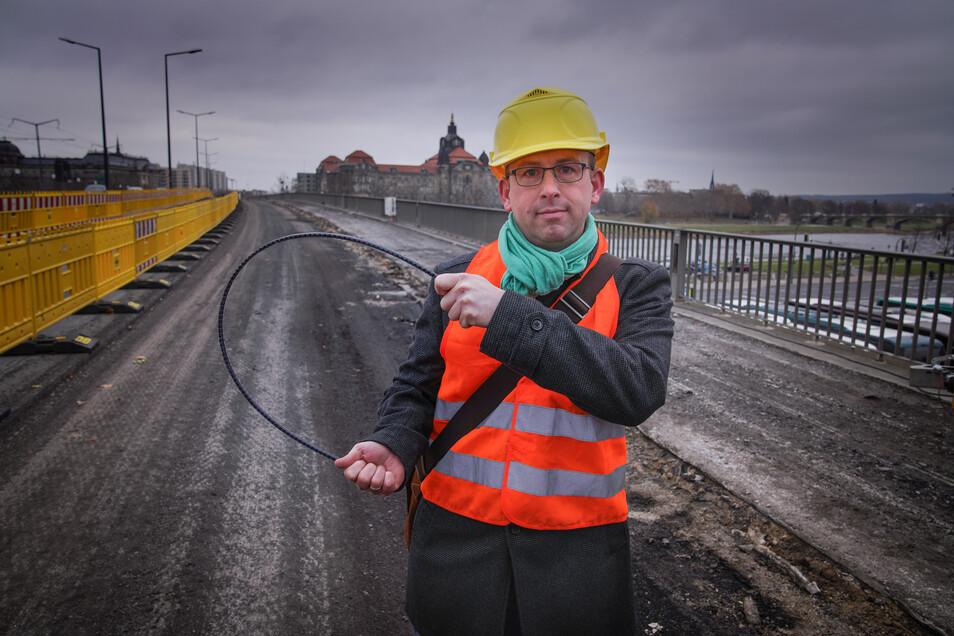 Brücken-Abteilungsleiter Andreas Gruner zeigt auf der Carolabrücke einen der neuartigen Basalt-Bewehrungsstäbe. Dieses leichte und flexible Material ermöglicht es, dass der Geh- und Radweg bei der Sanierung um einen knappen Meter verbreitert wird.