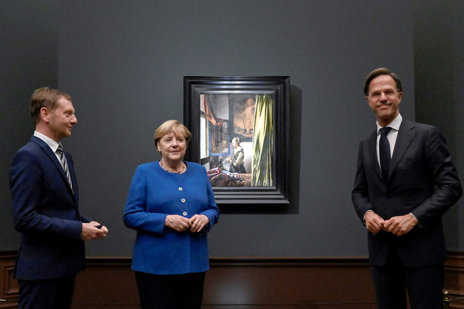 """Michael Kretschmer (CDU), Bundeskanzlerin Angela Merkel (CDU) und Mark Rutte, Ministerpräsident der Niederlande vor Vermeers berühmten Gemälde """"Brieflesendes Mädchen""""."""