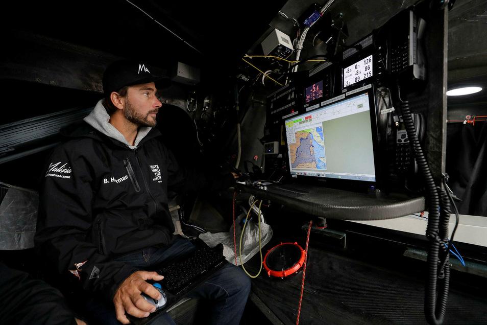 """Skipper Boris Herrmann sitzt auf der emissionsfreien Rennjacht """"Malizia"""" unter Deck im Navigationsbereich."""