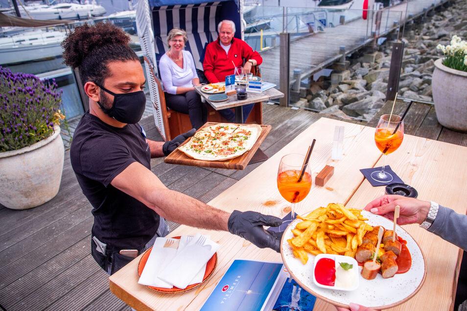 Im Landkreis Meißen und Sachsen erst ab 15. Mai möglich: Ein Kellner serviert in Kühlungsborn an der Ostsee mit Mundschutz und Handschuhen seinen Gästen das Essen.